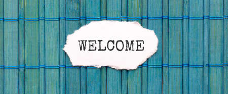 WELCOME text on the piece of paper on the green wood background