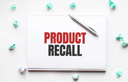 Blank sheet, pen and crumpled paper balls on gray table, flat lay. PRODUCT RECALL