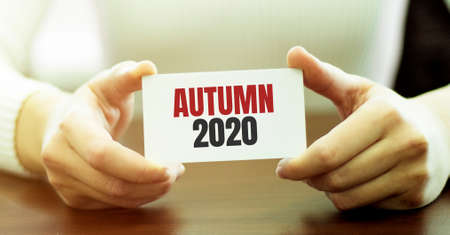 Businesswoman holding a card with text Autumn 2020
