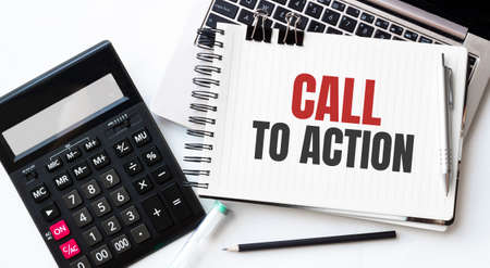 Keyboard of laptop, calcualtor, pencil and notepad with text CALL TO ACTION on the white background