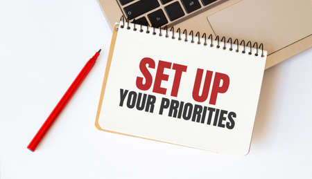 Laptop, red pen and notepad with text Set up your priorities in the white background