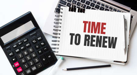 Keyboard of laptop, calcualtor, pencil and notepad with text TIME TO RENEW on the white background