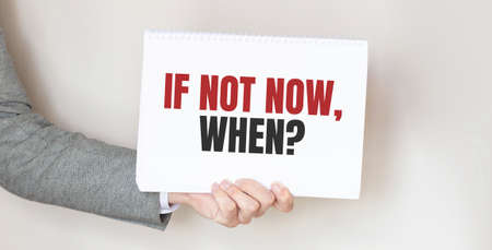 businessman holding a card with text IF NOT NOW WHEN