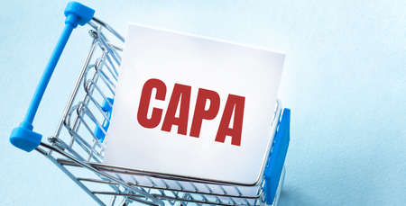 Shopping cart and text CAPA on white paper note list. Shopping list concept on blue background. Stok Fotoğraf