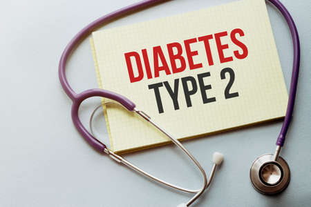 On a purple background a stethoscope with yellow list with text diabetes TYPE 2 Stock fotó