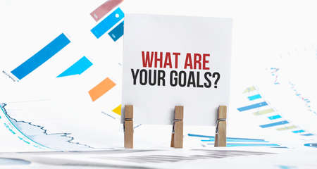 WHAT ARE YOUR GOALS text on paper sheet with chart, dice, spectacles, pen, laptop and blue and yellow push pin on wooden table - business, banking, finance and investment concept