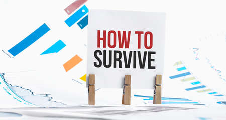 HOW TO SURVIVE text on paper sheet with chart, dice, spectacles, pen, laptop and blue and yellow push pin on wooden table - business, banking, finance and investment concept