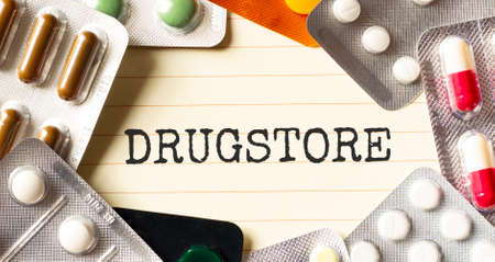 Text DRUGSTORE on a white background. Nearby are various medicines. Medical concept.