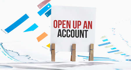 OPEN UP AN ACCOUNT text on paper sheet with chart, dice, spectacles, pen, laptop and blue and yellow push pin on wooden table - business, banking, finance and investment concept
