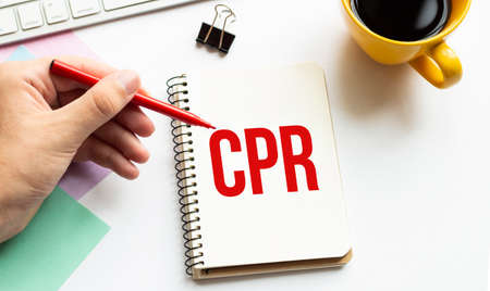 Hand with red pen. Cofee cup. Stick. Keyboard and white background. CPR sign in the notepad