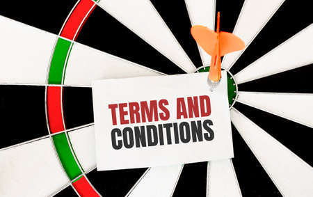 Handwriting TERMS AND CONDITIONS on notepaper with dart arrow and dart board.