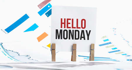 HELLO MONDAY text on paper sheet with chart, dice, spectacles, pen, laptop and blue and yellow push pin on wooden table - business, banking, finance and investment concept Banco de Imagens