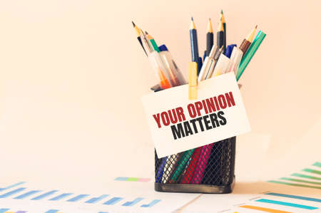 Card with text YOUR OPINION MATTERS on the pen box in the office. Diagram and white background. Stock Photo