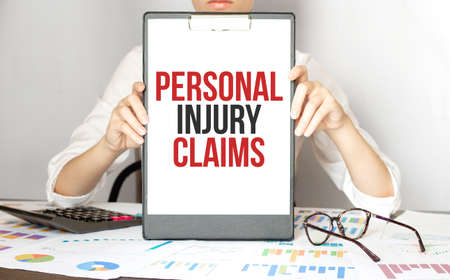 businesswoman holding a card with text PERSONAL INJURY CLAIMS Banque d'images