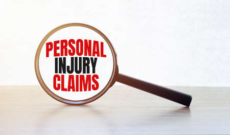Magnifying glass with text PERSONAL INJURY CLAIMS on wooden table.