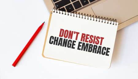Laptop, red pen and notepad with text Dont resist change embrace in the white background