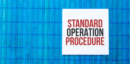 blank note pad with text STANDARD OPERATION PROCEDURE on blue wooden background