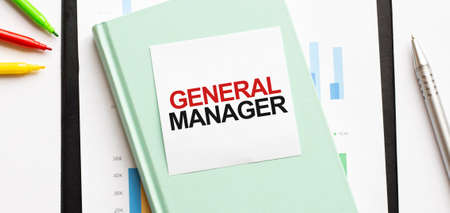 Financial diagram on white big notepad, green book and paper sheet with text GENERAL MANAGER. Business concept