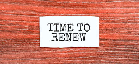 TIME TO RENEW text on the piece of paper on the red wood background