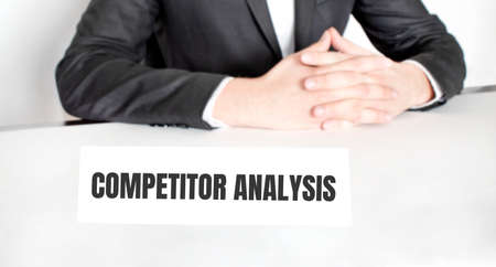 Businessman sitting at the table and signboard with text COMPETITOR ANALYSIS