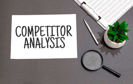 Top view of magnifying glass, calculator, pen, plant and notebook written with COMPETITOR ANALYSIS sign Standard-Bild