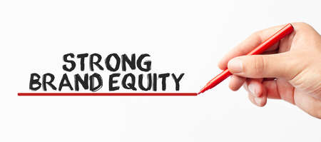 Hand writing STRONG BRAND EQUITY with red marker. Isolated on white background. Business, technology, internet concept. Stock Image