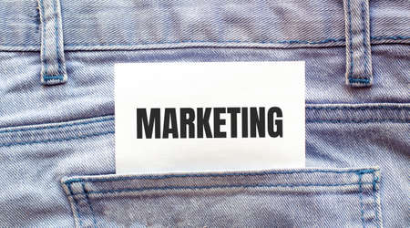 MARKETING words on a white paper stuck out from jeans pocket. Business concept