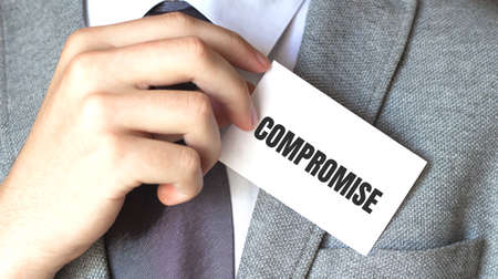 businessman holding a card with text COMPROMISE