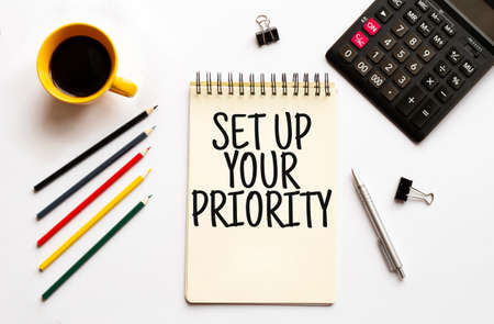 Cofee cup, calculator, notepad, pen and pencils on the white background. Business concept. Text SET UP YOUR PRIORITY