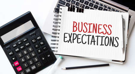 Keyboard of laptop, calcualtor, pencil and notepad with text BUSINESS EXPECTATIONS on the white background