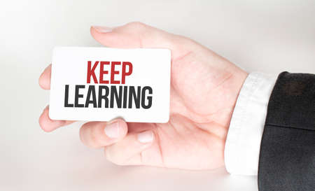 businessman holding a card with text KEEP LEARNING