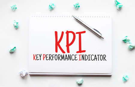 Blank sheet, pen and crumpled paper balls on gray table, flat lay. Text kpi key performance indicator