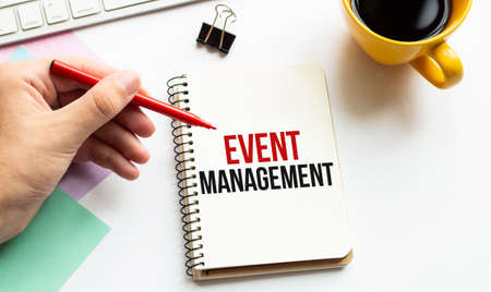 Hand with red pen. Cofee cup. Stick. Keyboard and white background. EVENT MANAGEMENT sign in the notepad