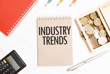 Calculator, red notepad, three color pencils, silver pen and brown notebook with text INDUSTRY TRENDS