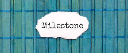 MILESTONE text on the piece of paper on the green wood background