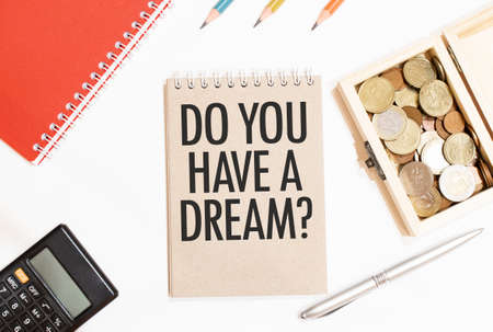 Calculator, red notepad, three color pencils, silver pen and brown notebook with text DO YOU HAVE A DREAM