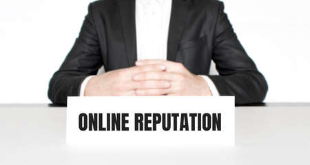 Businessman sitting at the table and signboard with text ONLINE REPUTATION. Business concept Stock fotó