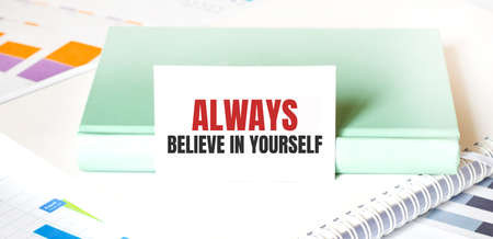 Financial diagram on white big notepad, green book and paper sheet with text Always believe in yourself. Business concept