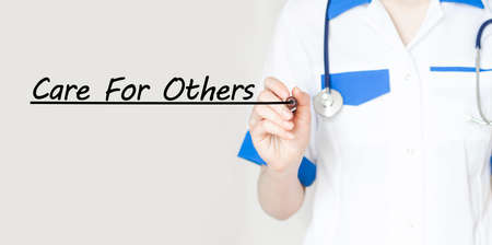 Doctor holding a marker with text CARE FOR OTHERS medical concept 版權商用圖片