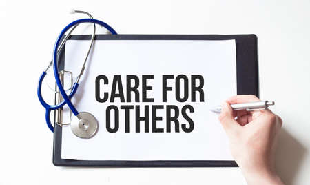 Doctor holding a card with text CARE FOR OTHERS, medical concept