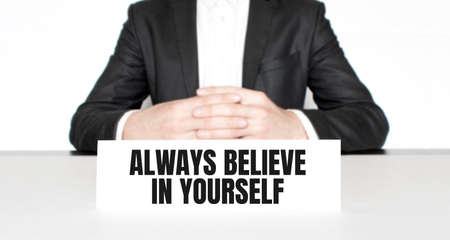 Businessman sitting at the table and signboard with text Always believe in yourself. Business concept