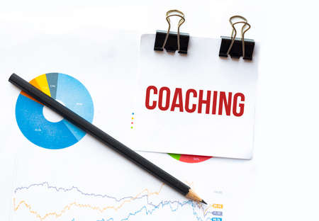 Notepad with text COACHING on business charts and pen