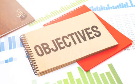 Word writing text OBJECTIVES on notepad. Business concept with red notepad and financial amounts. Stock fotó