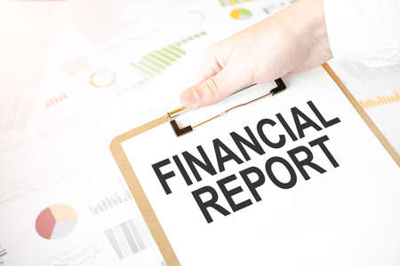 Text FINANCIAL REPORT on white paper plate in businessman hands with financial diagram. Business concept
