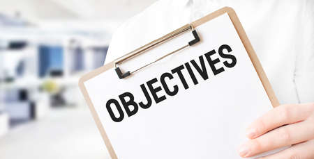 Text OBJECTIVES on white paper plate in businessman hands in office. Business concept Stock fotó