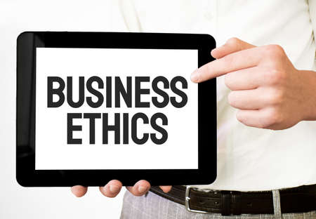 Text BUSINESS ETHICS on white paper plate in businessman hands on the white bakcground. Business concept Stock fotó