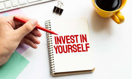 Hand with red pen. Cofee cup. Stick. Keyboard and white background. Invest in Yourself sign in the notepad Stock fotó
