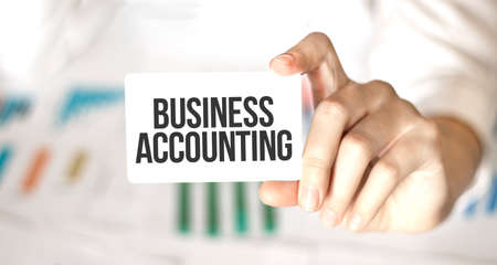 businesswoman holding a card with text business accounting