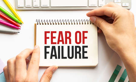 businesman hold notepad with text Fear of Failure White background. Business