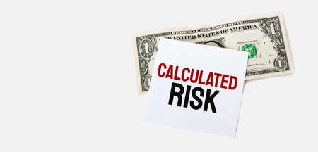 1 dollar bill and white notepad sheet on the white background. Calculated risk text. Stock fotó